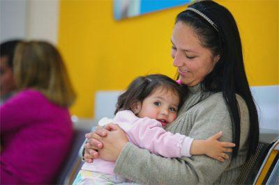Madre lleva a su pequeña hija hacia su primera consulta oftalmológica para la evaluación de miopía infantil en el centro de salud visual salauno