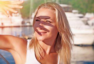 Mujer tapándose con la mano de los rayos del sol en el verano