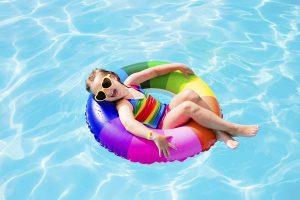 Niña en la piscina en el verano con lentes de sol para protegerse de los rayos uv